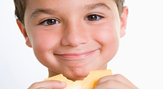 boy snacking on a piece of cheese