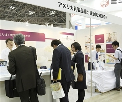 Booth visitors talk to USDEC staff at trade show in Tokyo